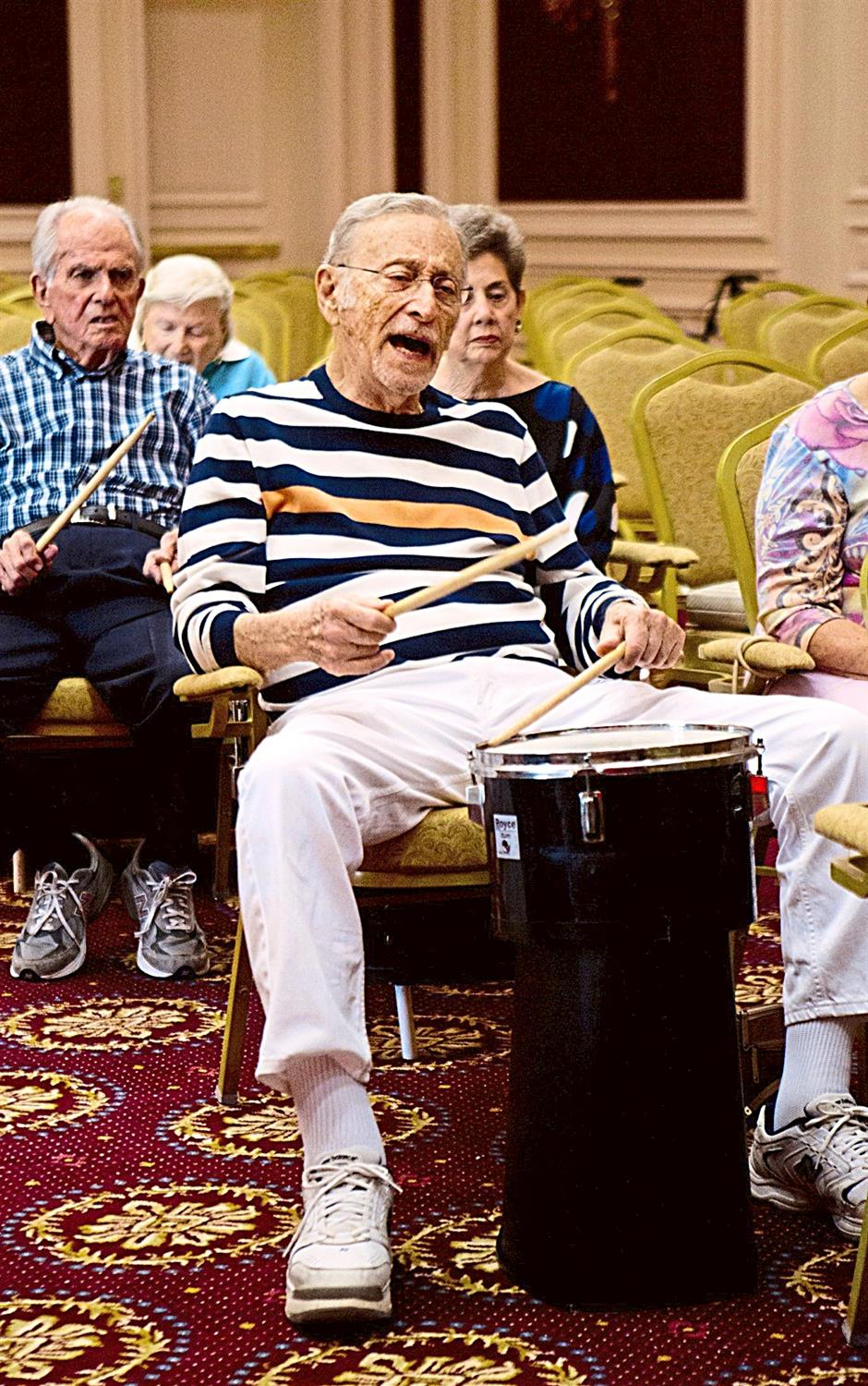 Sam Nevel and other residents of The Palace in Coral Gables, Florida, participating in a drum circle. Music brings back happy memories and mends grieving hearts.
