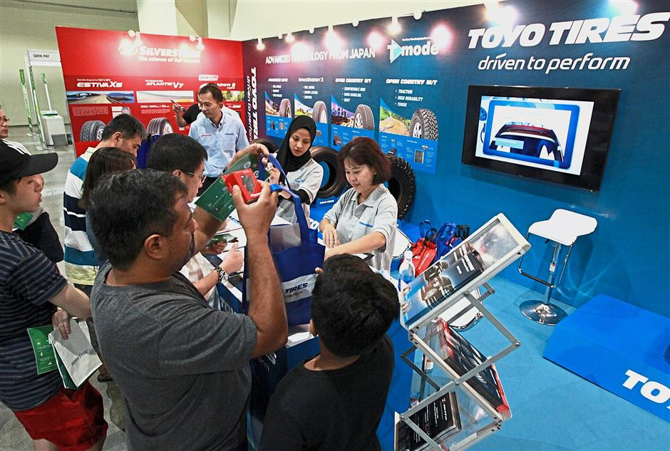 Visitors registering at the Toyo booth for door gifts such as hand fans, mineral water, windscreen stickers and keychains.