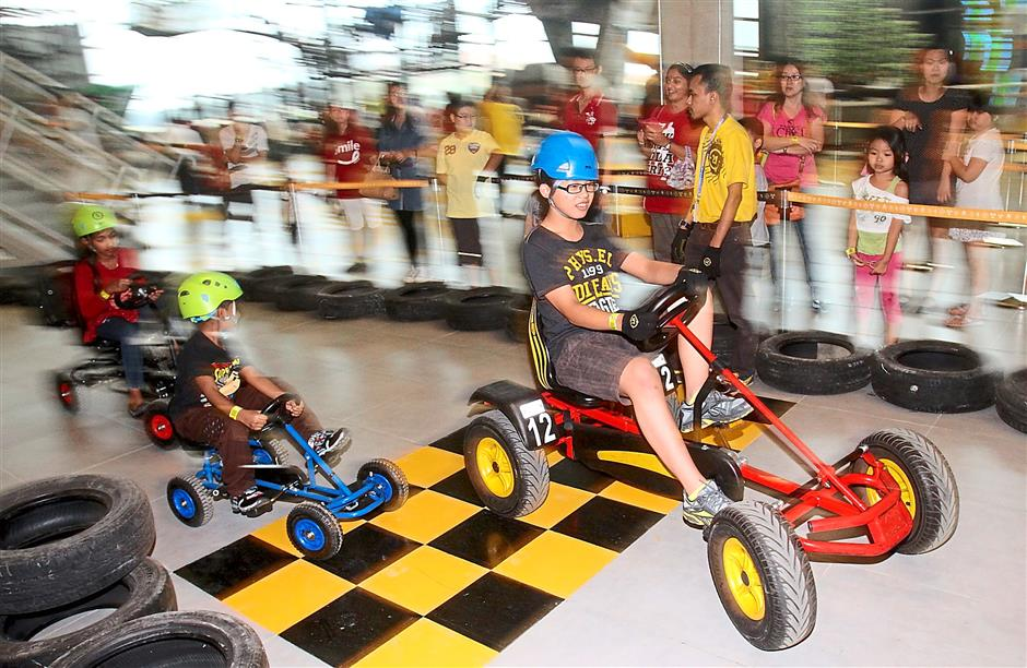 Children cycling through the Go Pedal with their human-powered karts around the 100m track.