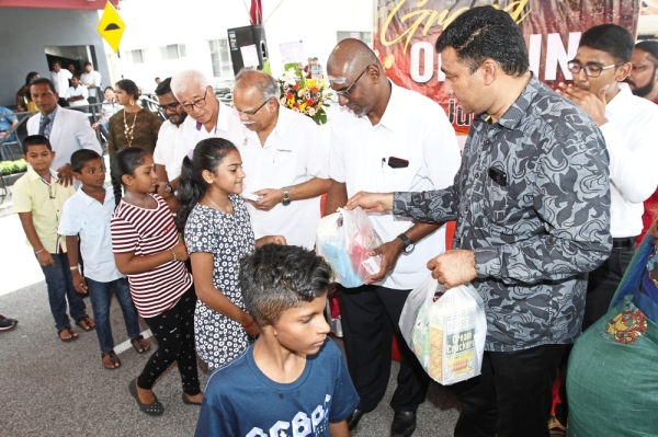 (From right) Harikrishnan, Rayer, Ramasamy and Phee giving out goodie bags to the needy at the opening of the new cafe.