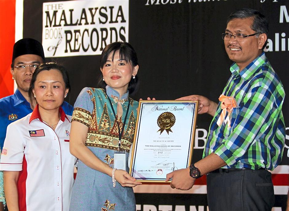 Shamsul (right) presenting the certificate to Ngok for the achievement.