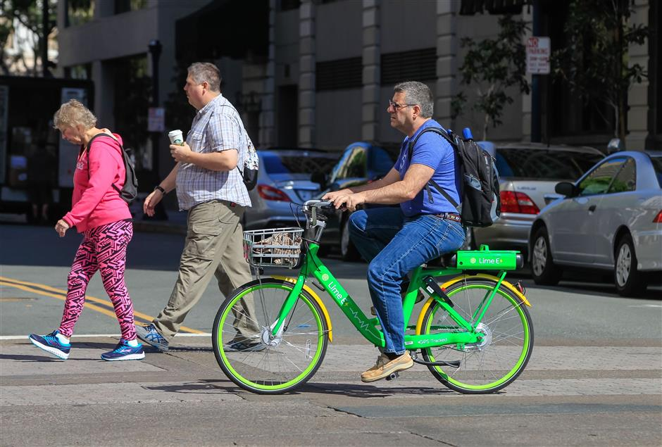 A person rides a LimeBike bike along Broadway in downtown San Diego on March 1, 2018. (Eduardo Contreras/San Diego Union-Tribune/TNS)