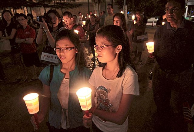 Saving ener gy: Shoppers g etting in to the Earth Hour mood with candles to support the caus e. — filepic