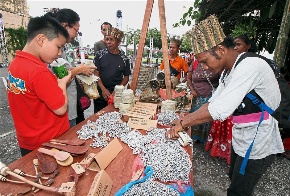 Visitors checking out handicraft made by orang asli at the event.