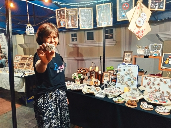 Wong showing some of the colourful stones with meaningful messages sold at her stall.