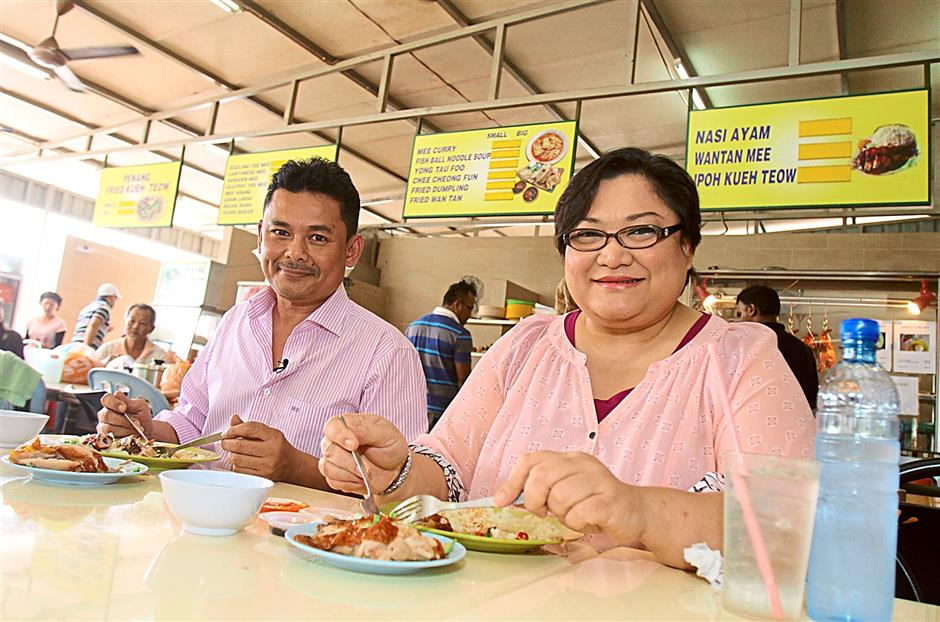 Suria FM DJs Halim Othman (left) and Adibah Noor enjoying their chicken rice at Barry's stall in Restoran Jamal Mohamed, Kelana Jaya. The duo will be on the panel of judges for the Star People's Food Awards.