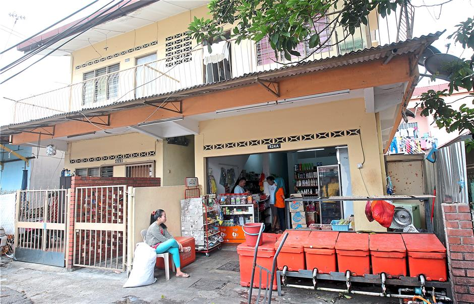 An example of a house converted into a hostel, with tenants living upstairs while also doing business downstairs. This is also an example of an unregulated foreign worker hostel.