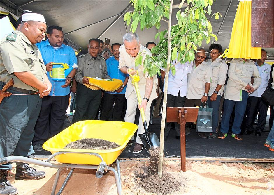 Sultan Nazrin Muizzuddin Shah planting a tree during the launching ceremony of the Central Forest Spine Ecology Corridor Viaduct at the East West Highway near Banding.