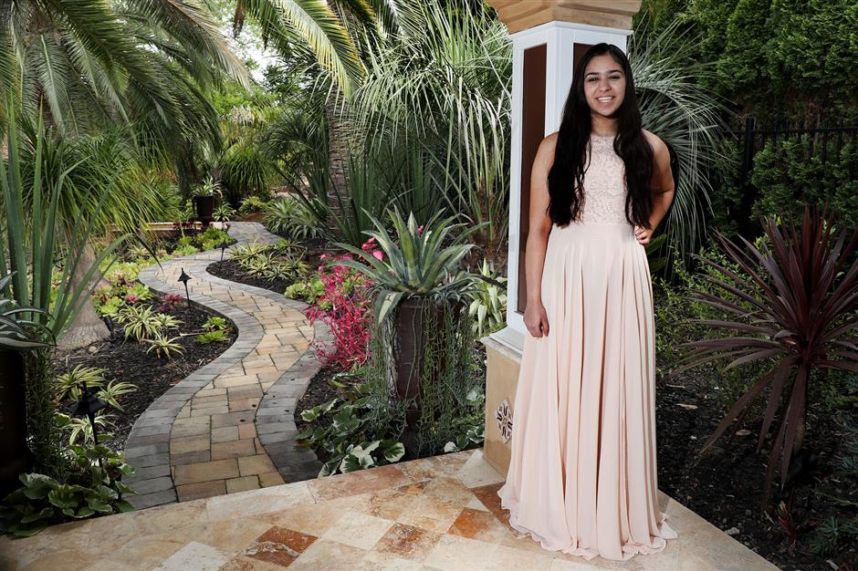 Riya Gupta, 17, of Saratoga, poses with a prom dress at her classmate's home Nishka Ayyar, 16, in Saratoga, Calif., on Wednesday, April 18, 2018. The junior high school students built the PromElle app designed for renting prom dresses to and from their users. (Ray Chavez/Bay Area News Group/TNS)