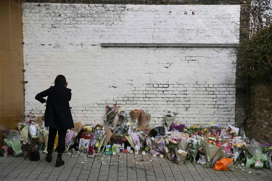 A family friend looks at flowers and messages left at a temporary memorial, set up at a spot near to where 18 year old Israel Ogunsola was stabbed to death on Wednesday April 4, in central Hackney, north London on April 6, 2018. Another deadly night in London is putting pressure on political leaders, as a surge in violence on the streets of the British capital pushes its murder rate higher than New York's. / AFP PHOTO / Daniel LEAL-OLIVAS