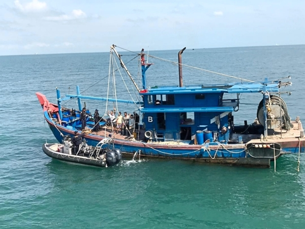 Security measure: An MMEA vessel inspecting a trawler in the waters off Johor as part of Ops Jaksa.