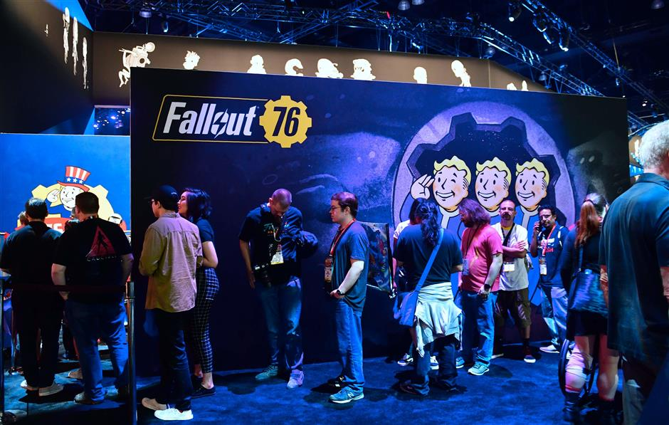 Gaming fans wait in line for freebies from Bethesda\'s \'Fallout 76\' game at the 24th Electronic Expo, or E3 2018 in Los Angeles, California on June 13, 2018, where hardware manufacturers, software developers and the video game industry present their new games between June 12-14. / AFP PHOTO / Frederic J. BROWN
