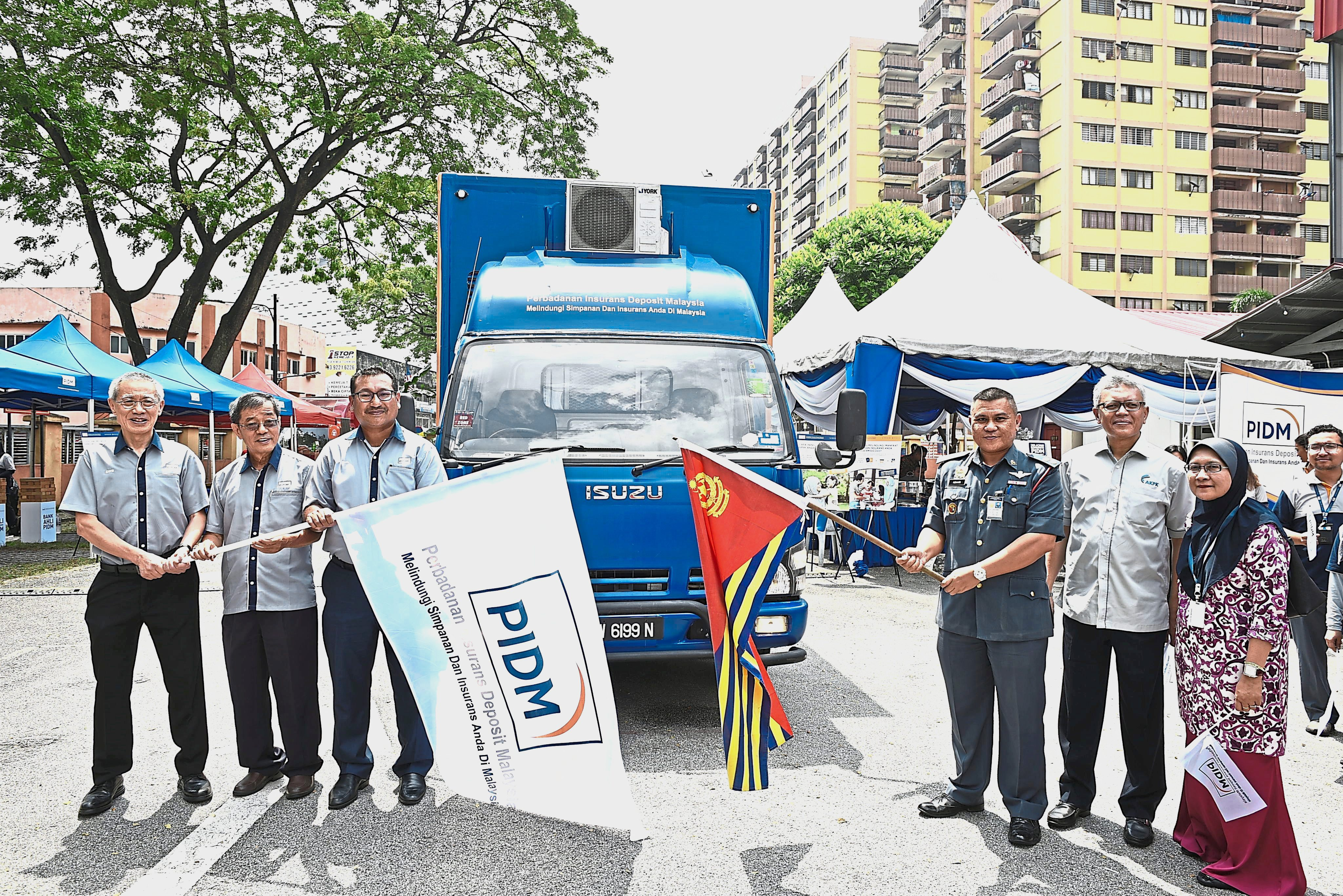 Rafiz (third from left) and Fire and Rescue Department fire safety division assistant director Ashari Johari (in  uniform) flagging off the PIDM roving truck at the Fire and Rescue Department headquarters in Jalan Hang Tuah, Kuala Lumpur.