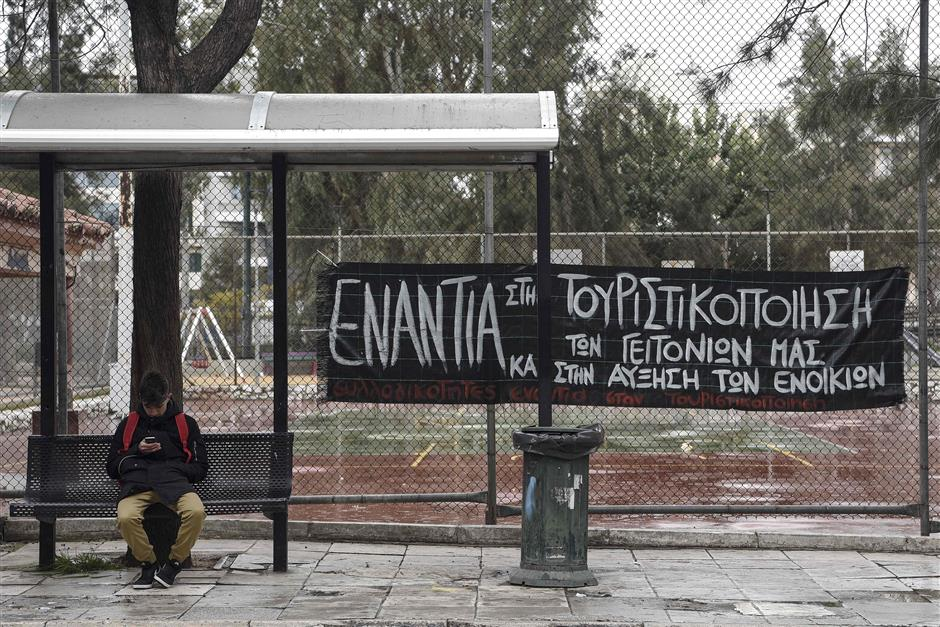 A man sits by a banner reading 'No to tourism and the gentrification of our neighbourhood - No to raise of the rents' in Koukaki area in Athens, which in 2016 was named Airbnb's fifth fastest growing neighbourhood globally with an 800-percent jump in home-sharing. The banner reads. - The Greek chamber of hotels commissioned a Grant Thornton study that found that over 76,000 properties in Greece are available on home-sharing platforms. The study argued that declining availability had pushed up rents in central Athens by 9.3 percent in a year, disproportionately affecting poorer sections such as pensioners and single-parent families. (Photo by LOUISA GOULIAMAKI / AFP)
