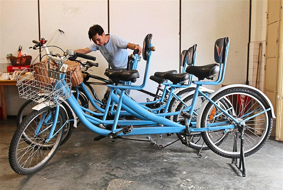 Safety-conscious: Chiang checking the brakes on his tandem bicycles at his outlet in Gat Lebuh Pasar.