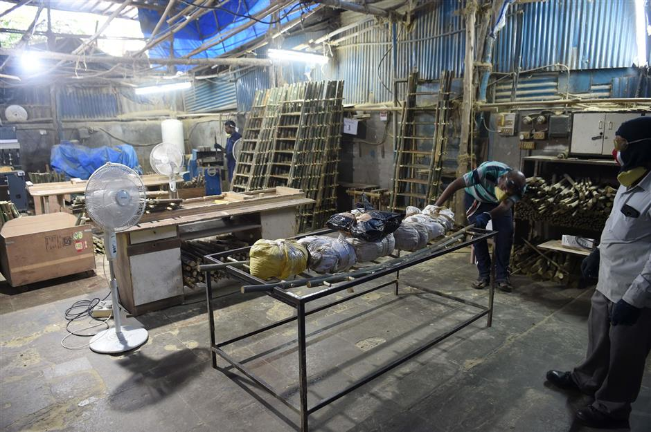 In this photo taken on September 19, 2018 a worker tests the load bearing capacity of a funeral cot, part of the SarvaPooja 'final rites kit' at their manufacturing unit, in Mumbai. - When Parag Mehta had to arrange a second family funeral in two weeks he was distraught and short of time to get the 38 items for an elaborate Hindu ceremony -- so he went online and found a 'final rites kit'. (Photo by INDRANIL MUKHERJEE / AFP) / TO GO WITH: India-economy-internet-Amazon-death, FOCUS by Vishal MANVE