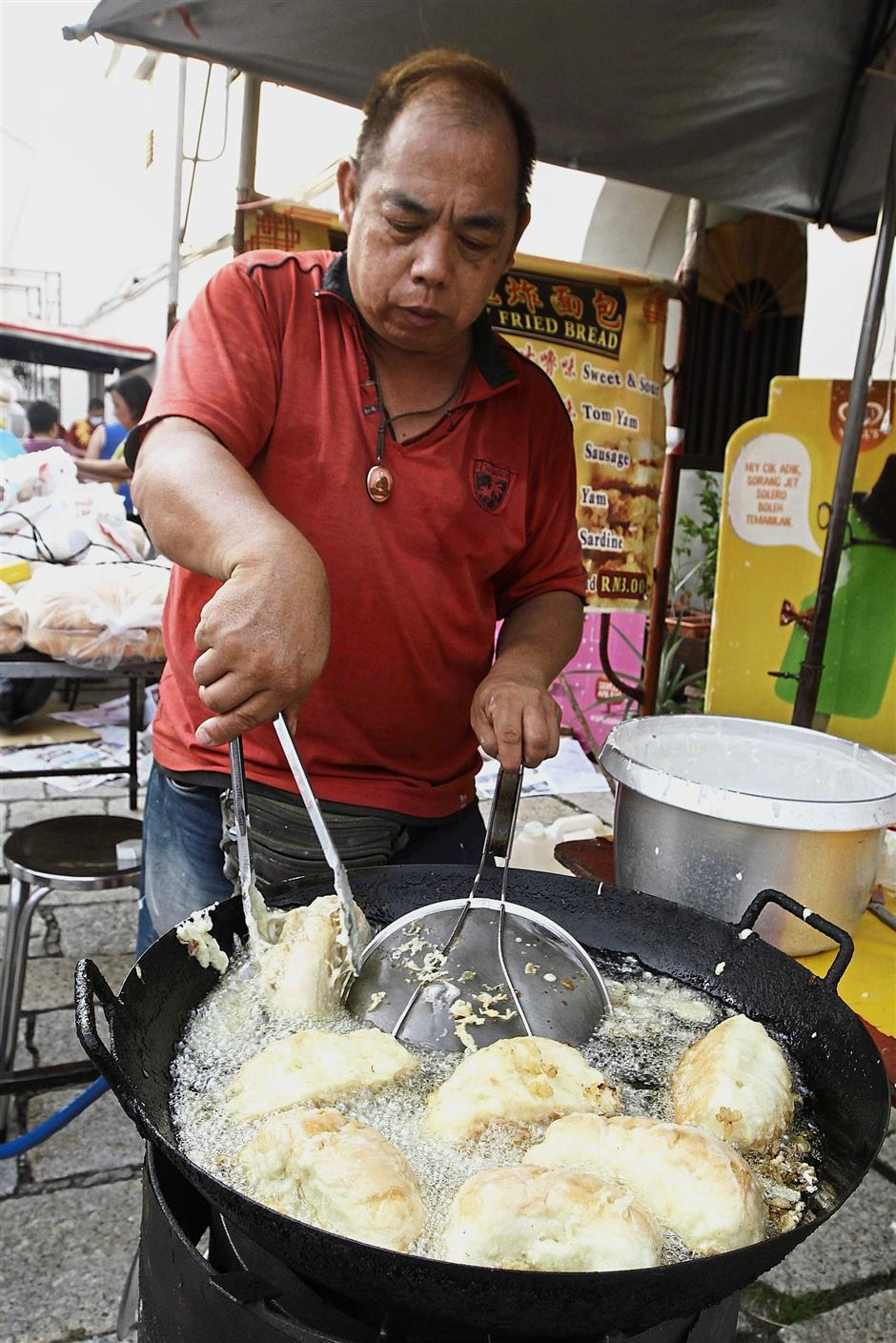 A hawker busy preparing fried bread snacks at one of the stalls.
