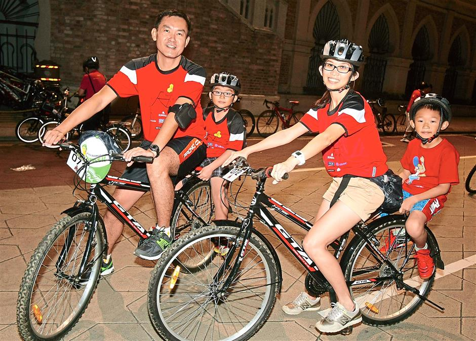 Happy family: (from left) Hiew Kok Leong, 40, Hiew Yuk Wei, 8, Tan Bee Hong, 35, and Hiew Yuk Ming, 7, during the KLSCCCIs Carbon Neutral Activities 2 - KL City Eco Charity Bicycle Ride
