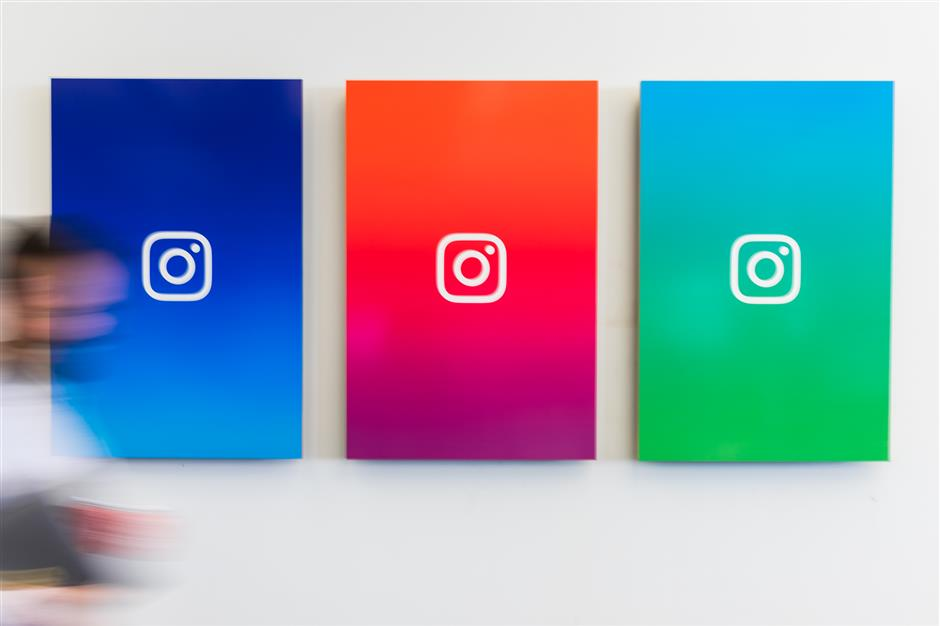 An employee walks past branded posters displayed at the Instagram Inc. office in New York, U.S., on Monday, June 4, 2018. Once, Instagram was a simple photo-sharing app, a way for iPhone shutterbugs to show off their latest cool pics. Now, its visual nature and 1 billion active users have sellers salivating over its potential as a place to sell everythingu00a0from dresses to furniture. Photographer: Jeenah Moon/Bloomberg