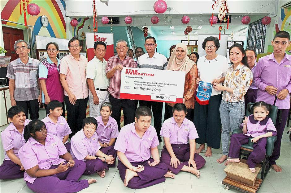 Kind gesture: Siti Aishah (fourth from right) presenting the mock cheque to Cheong. Looking on is Hoh (centre).