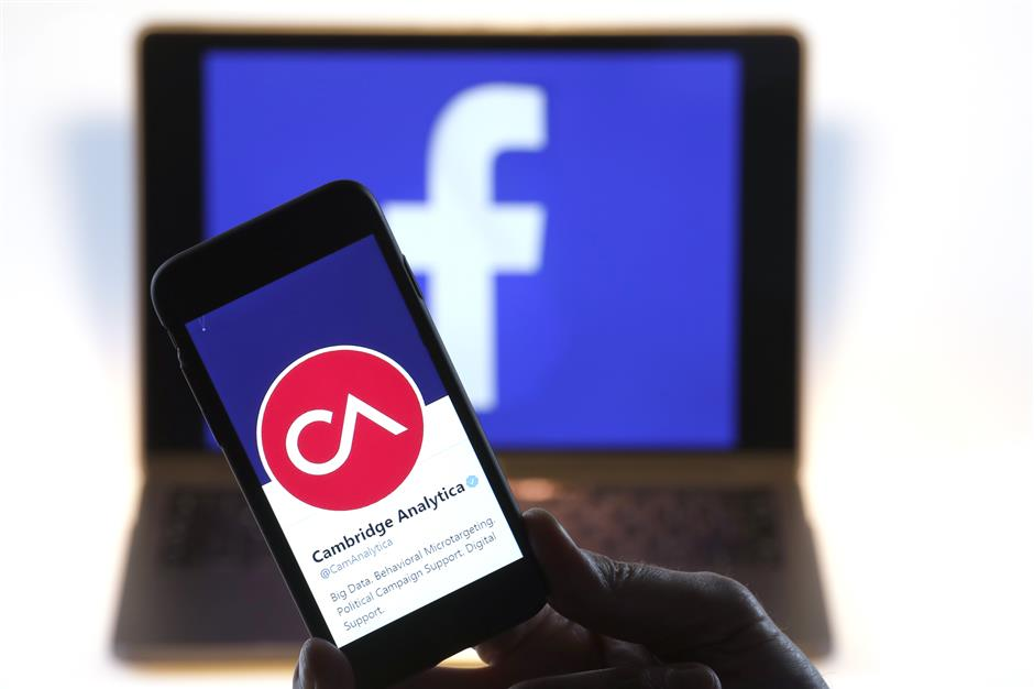 The verified Twitter Inc. page of Cambridge Analytica, displaying their logo and company name, sit on an Apple Inc. iPhone against a backdrop of the Facebook Inc. sign shown on a computer screen in this arranged photograph in London, U.K., on Thursday, March 22, 2018. Facebook Inc.u2019s co-founder and chief executive officer Mark Zuckerberg has been called to appear before a House panel as fallout continues from revelations that Cambridge Analytica had siphoned data from some 50 million Facebook users as it built a election-consulting company that boasted it could sway voters in contests all over the world. Photographer: Luke MacGregor/Bloomberg