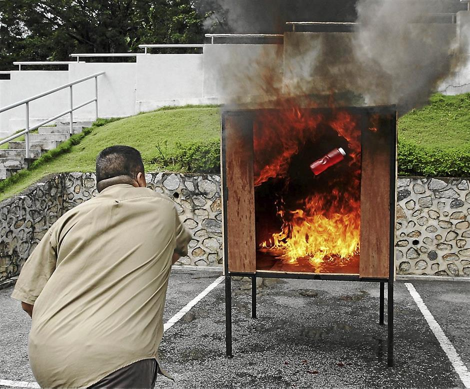 The use of a Flamoff extinguisher being demonstrated.