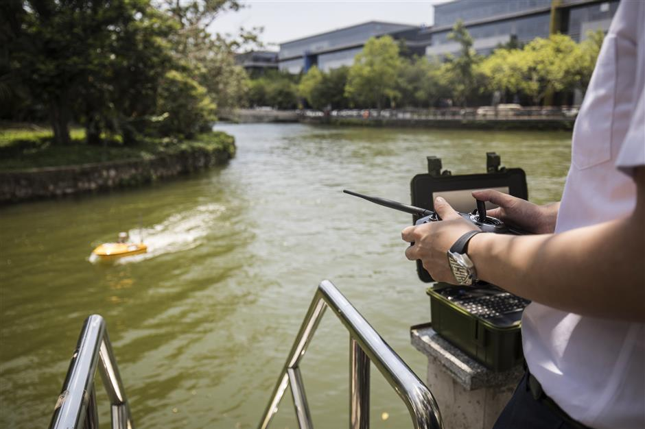 A technician manoeuvres an Oceanalpha Co. unmanned surface vessel in a pond using a remote control outside the company's offices in Zhuhai, China, on Thursday, May 18, 2018. Oceanalpha, one of a handful of companies around the globe specializing in ocean-going drones that operate on the surface, has fired the interest of some of China's biggest venture capitalists. Photographer: Qilai Shen/Bloomberg