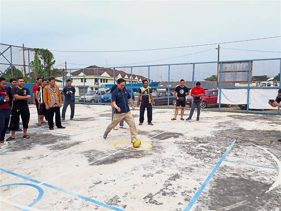 Puah kicking a ball to launch a futsal tournament at the Taman Manis community hall in Kulai.