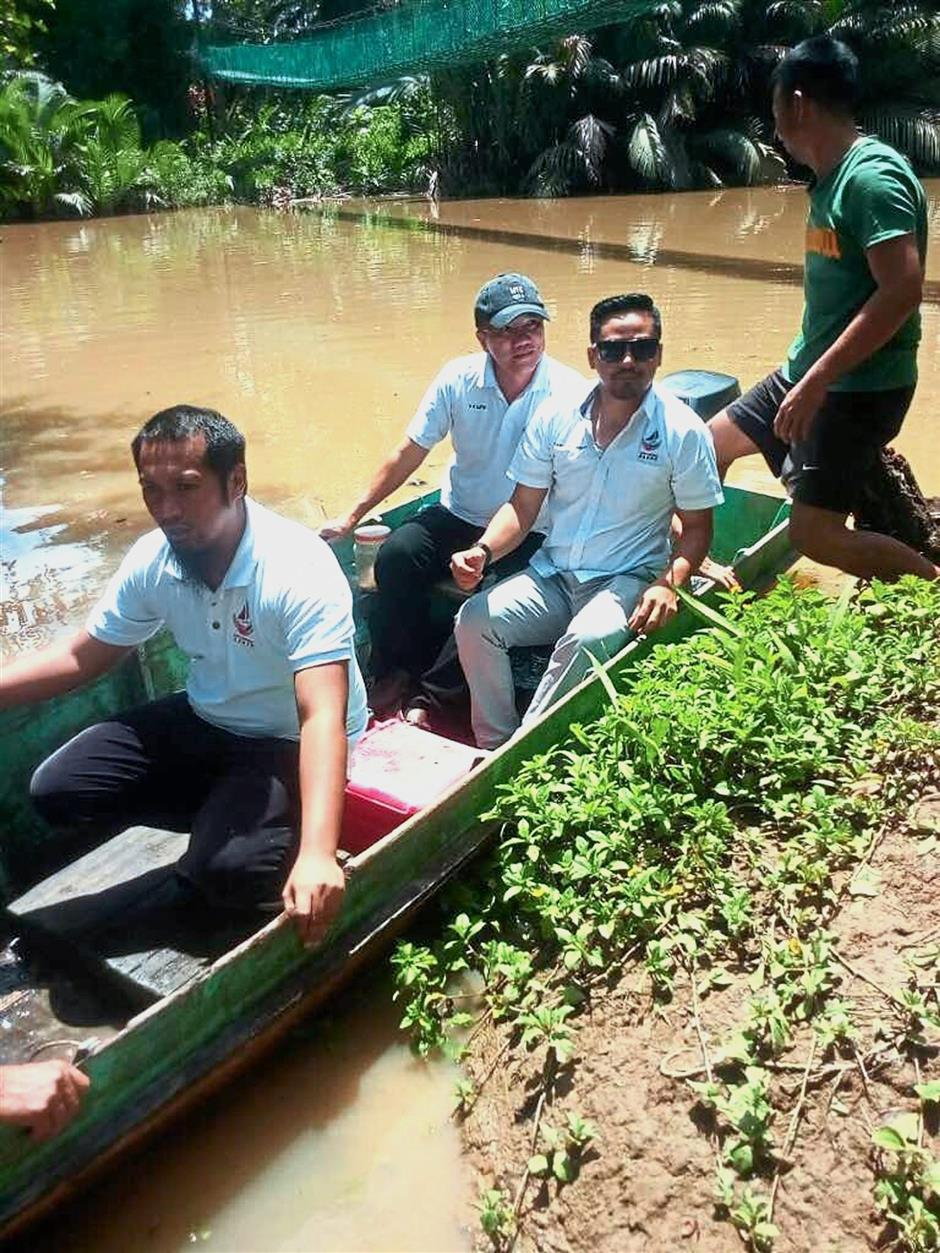 Making rounds: Liew (wearing green cap) and his officials preparing to check on the river.