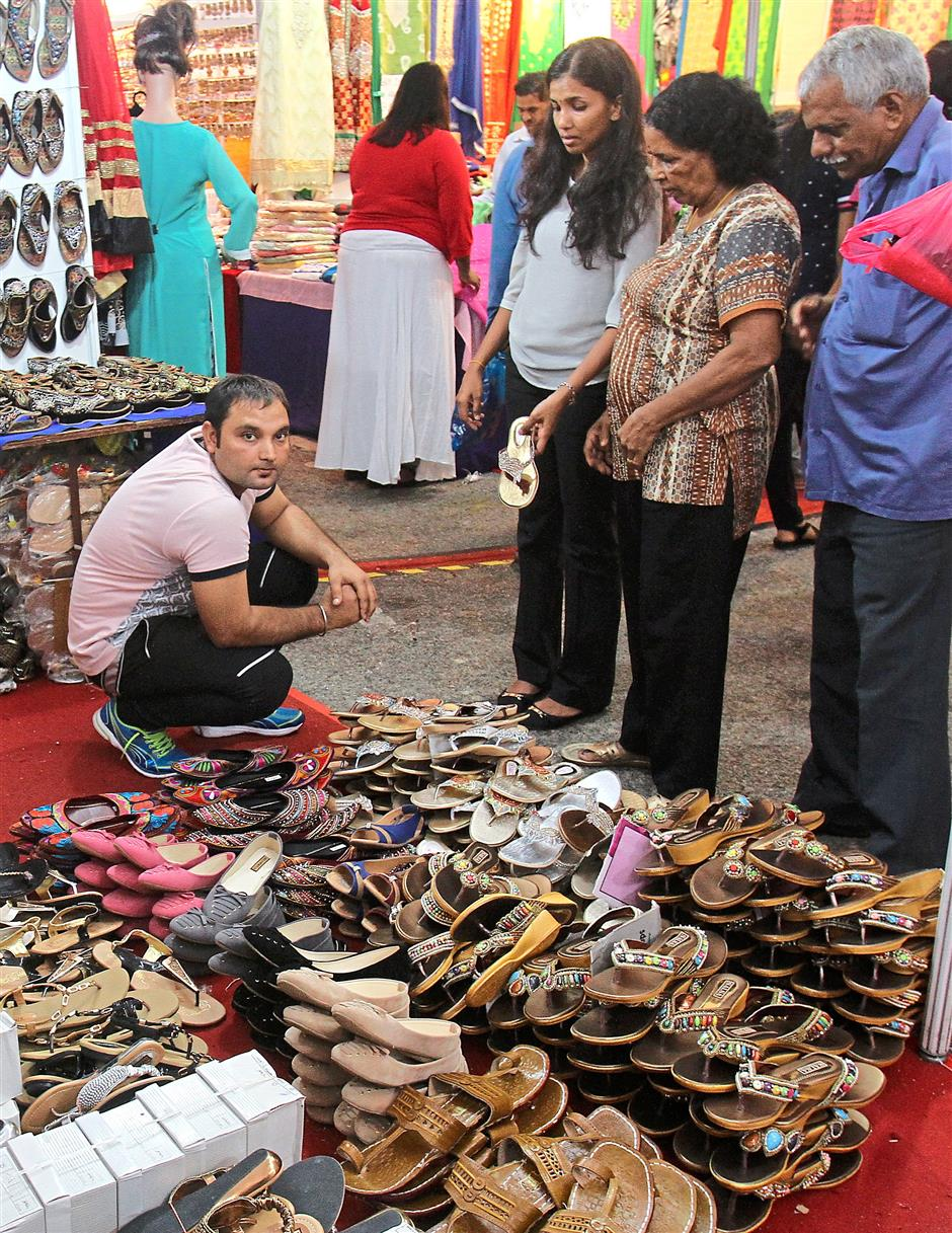 A family choosing traditional Indian sandals called chappals at the Akash Overseas booth which specialises in Indian traditional footwear.