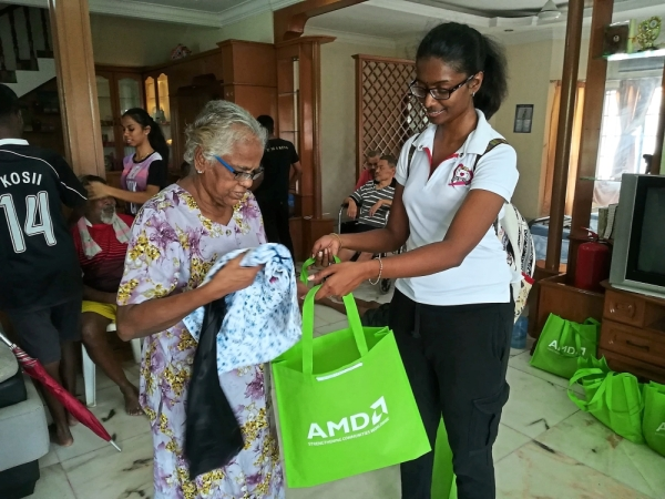 A volunteer from AMD presenting a goodie bag to a Destiny Starting Point resident.