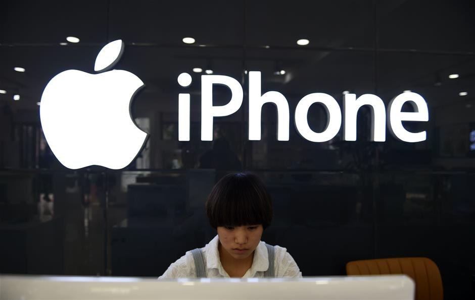 (FILES) In this file photo taken on September 16, 2014 a shop assistant works behind a computer at a store selling Apple products, including the iPhone, in Beijing. - Shares of Apple plunged at the start of trading on January 3, 2019, weighing on the broader market after the tech giant cut its sales forecast due to weakness in China.The tech-rich Nasdaq Composite Index fell 1.1 percent to 6,593.58, with Apple shedding 8.8 percent.The Dow Jones Industrial Average tumbled 1.0 percent to 23,106.83, while the broad-based S&P 500 slid 0.7 percent to 2,492.77. (Photo by Greg Baker / AFP)