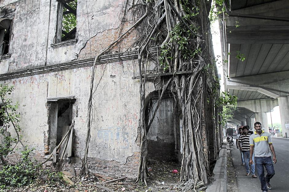 Derelict: Pedestrians walking past one of the abandoned shophouses that is overgrown with vegetation along Jalan Kem. The building was ravaged by fire several years ago.