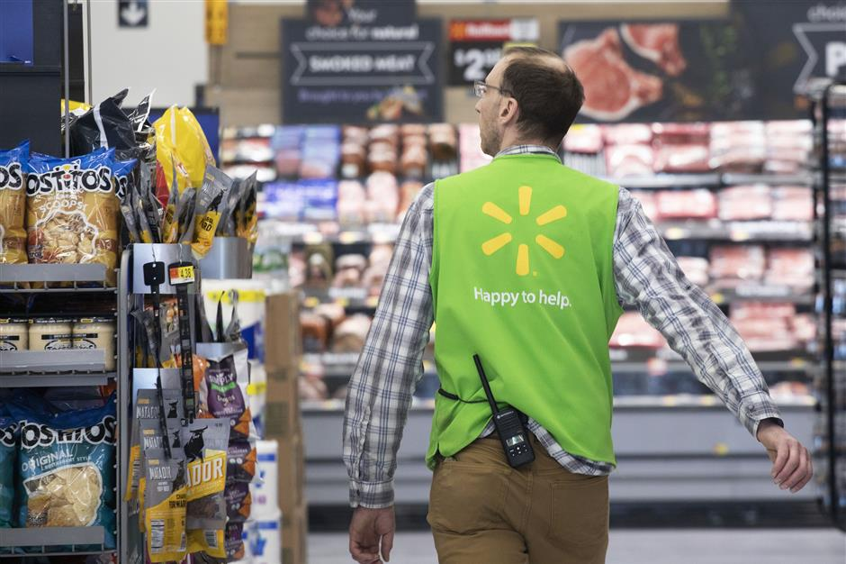 A Walmart associate works at a Walmart Neighborhood Market, Wednesday, April 24, 2019, in Levittown, N.Y.  Inside one of Walmartu2019s busiest Neighborhood Market stores, thousands of cameras suspended from the ceilings track when products are running low or when produce or meat start to lose their freshness. The technology is one of several features of a living lab that officially opens inside this store on Thursday. (AP Photo/Mark Lennihan)
