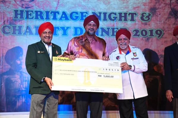 Gobind (centre) receiving a donation from Lt Col Mohan (right) at the fundraising dinner. With them is Malaysian Armed Forces Sikh Veterans Association president Major Baldev Singh.