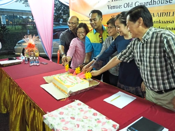 (From right) Hoh and Ng cutting the cake with other guests.