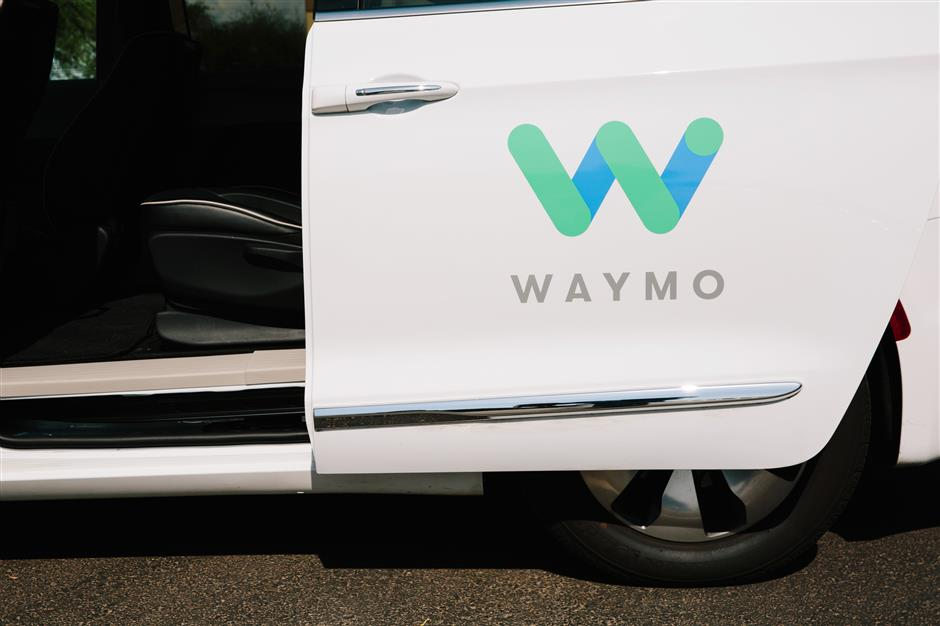 Waymo LLC signage is displayed on the open door of a Chrysler Pacifica autonomous vehicle in Chandler, Arizona, U.S., on Monday, July 30, 2018. The Google offshoot is tinkering with pricing and finalizing its business model for autonomous vehicles, which includes a new effort to boost public transit. Photographer: Caitlin O'Hara/Bloomberg