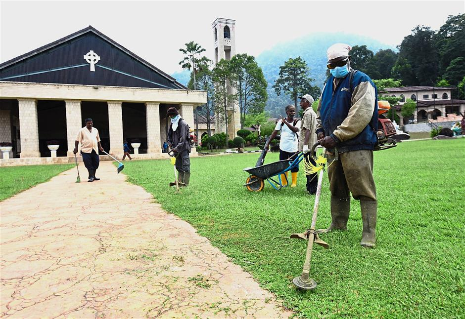 Church workers cutting grass in preparation for the Novena and Feast.