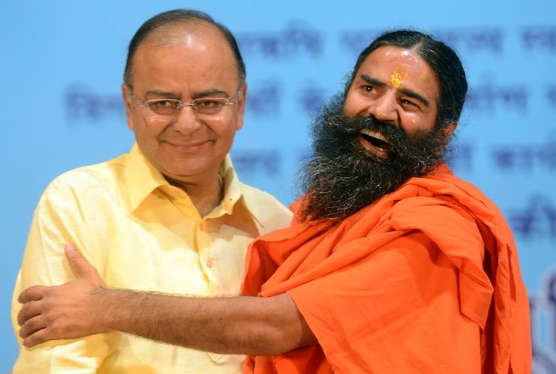 Indian yoga guru Baba Ramdev (R) greets Bharatiya Janata Party (BJP) senior leader Arun Jaitley during a rally in New Delhi on May 18, 2014. Jaitley has been made India\'s new finance minister as well as her defence minister - AFP Photo.