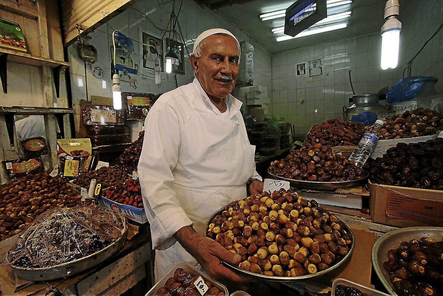 A vendor sells various kinds of dates at his stall in a market in Kuwait City. - AFP