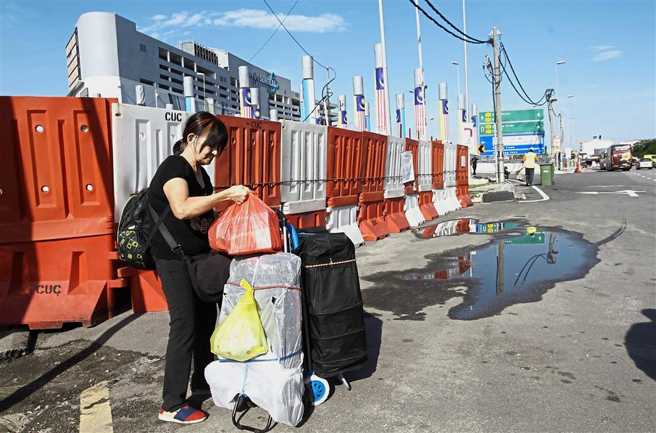 Brief Caption: Express buses dropping off passengers with their luggage by the roadside outside the closed-down temporary bus terminal near the Penang Sentral transportation hub in Butterworth.Star Pic by : LIM BENG TATT / The Star / 23 Nov 2018.