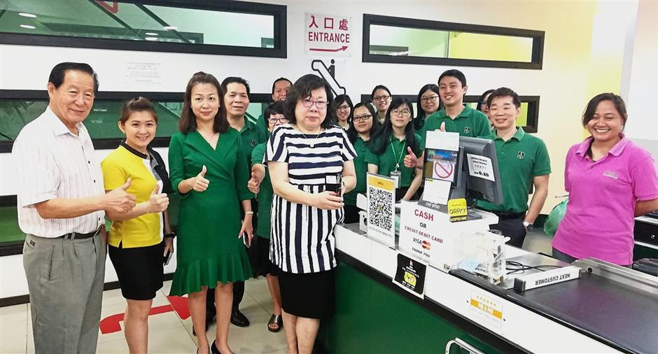 Hii (black and white stripe shirt) and Tiew (third from left) with staff members of the supermarket at the launch of the e-payment system.