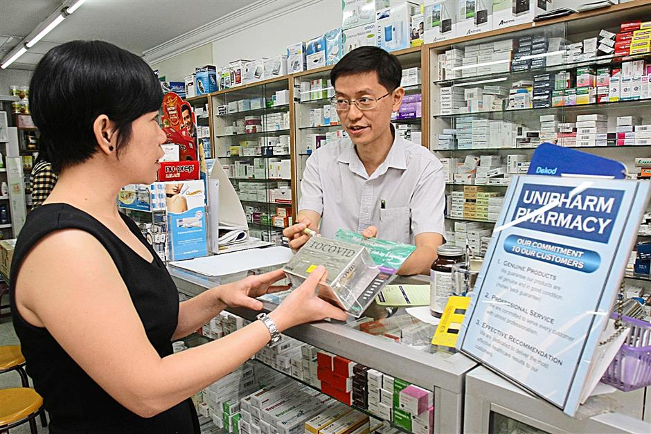 Unipharm Pharmacy, Subang Jaya, pharmacist Kevin Lee advising a customer on tocotrienol (vitamin E) supplements on July 10, 2014.