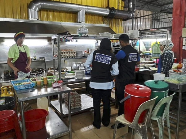 (Left pic) Health officers checking the kitchen of a restaurant. (Above) A foodoutlet is officially closed.