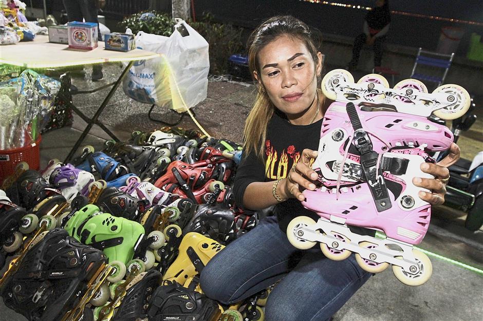 Operator Surayahani Mohd Shahab, 39, showing a pair of roller skates at her spot along Karpal Singh Drive.
