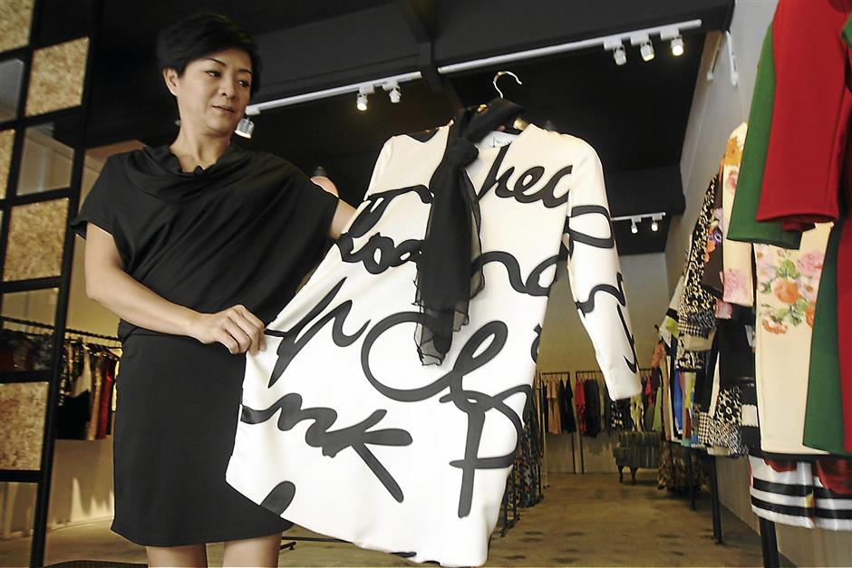 iplonline3009 7...Scents Couture owner Charmaine Low holding up a dress on sale at her boutique in Ipoh on Sept 27.