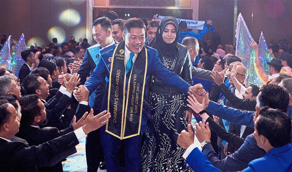 Shah Rizal Azmi being congratulated as he made his way to the stage with his wife Ku Sharmila and agency team members to receive his award for Champion CMC under the Direct Group category.