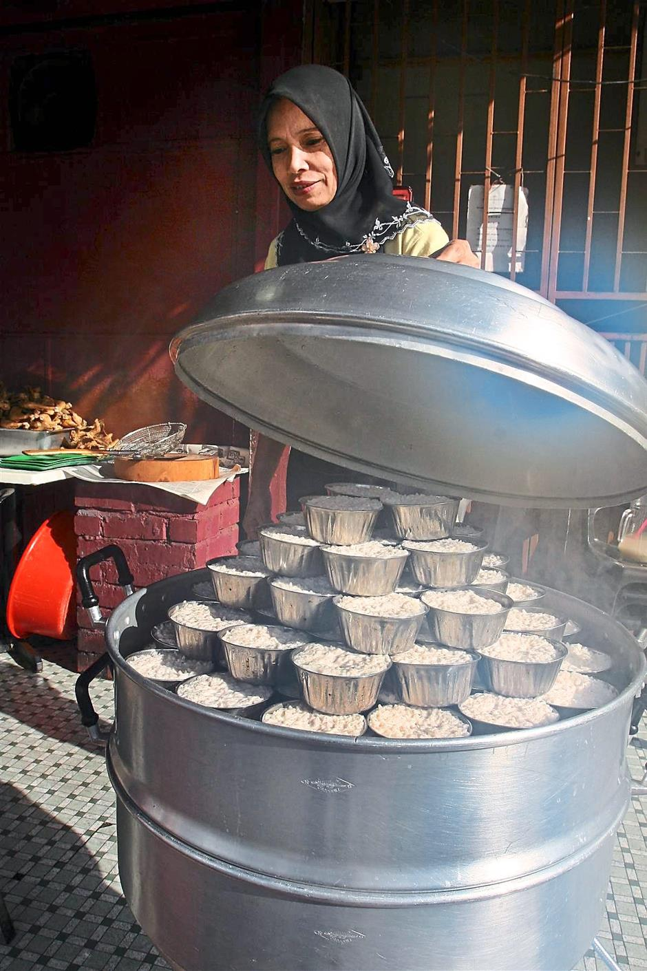 Piping hot: Rice being steamed inside a steam cooker at a shop in Ipoh. — filepic