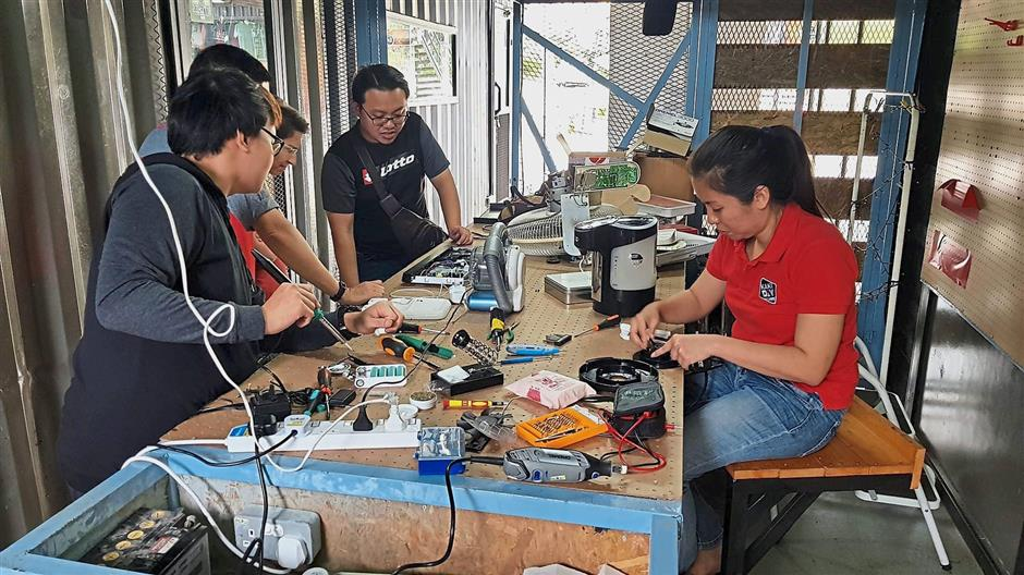 Kaki Repair volunteers discuss and help each other fix faulty items brought to them.