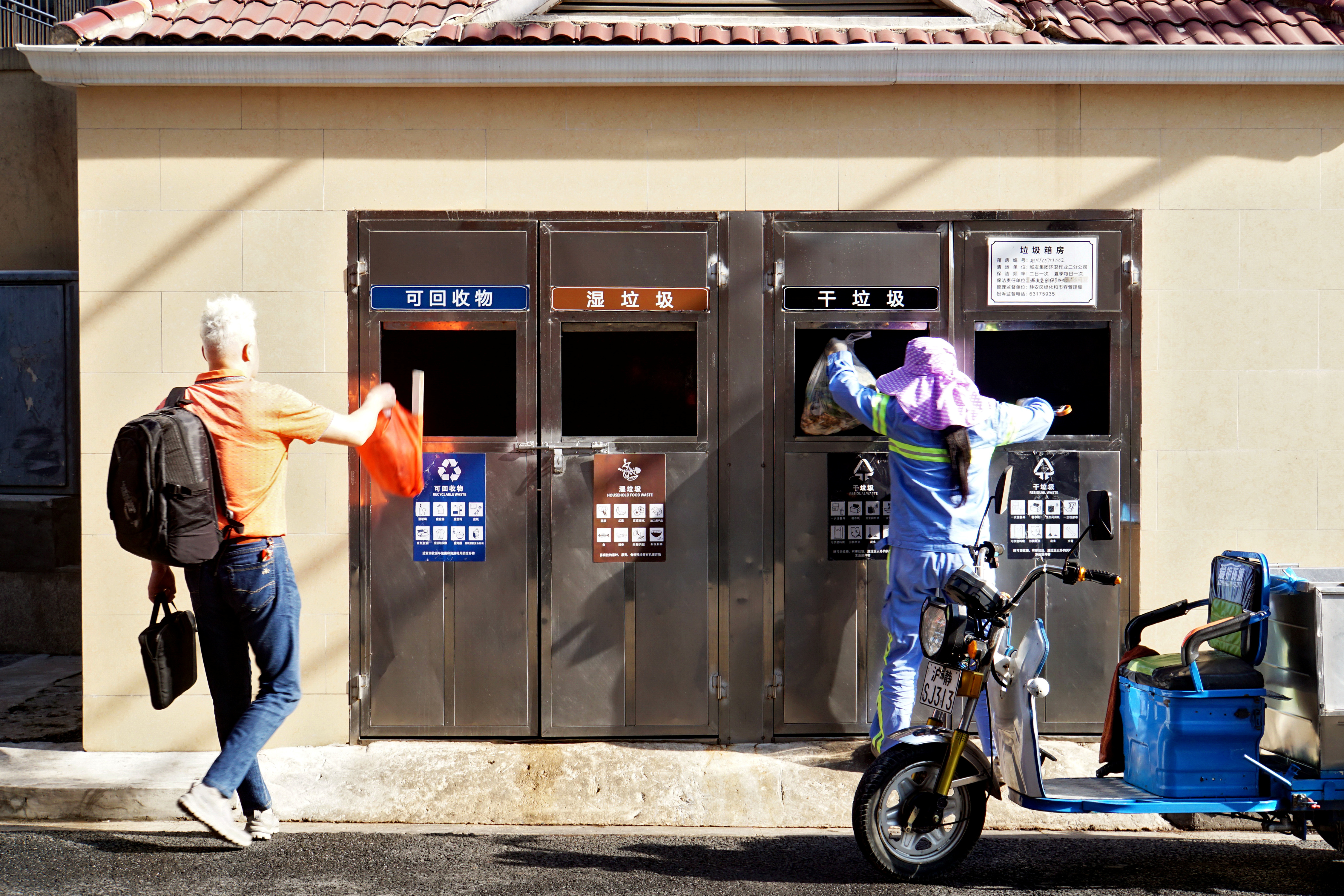 FILE PHOTO: A man and a cleaner throw trash at a separate waste collection in Shanghai, China May 24, 2019.  REUTERS/Stringer